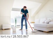 Купить «man in headphones cleaning floor by mop at home», фото № 28503867, снято 10 мая 2018 г. (c) Syda Productions / Фотобанк Лори