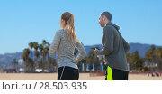 Купить «couple with earphones running over venice beach», фото № 28503935, снято 17 октября 2015 г. (c) Syda Productions / Фотобанк Лори