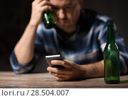 Купить «man with smartphone and bottle of beer at night», фото № 28504007, снято 24 ноября 2017 г. (c) Syda Productions / Фотобанк Лори