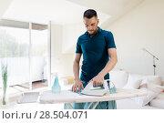 Купить «man ironing shirt by iron at home», фото № 28504071, снято 10 мая 2018 г. (c) Syda Productions / Фотобанк Лори