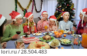 Купить «Happy family is talking at the table in time celebration New Year at home.», видеоролик № 28504483, снято 17 января 2018 г. (c) Яков Филимонов / Фотобанк Лори