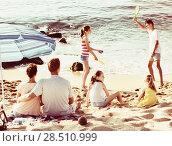 Купить «Couple relaxing on beach while their kids playing active games», фото № 28510999, снято 25 сентября 2018 г. (c) Яков Филимонов / Фотобанк Лори
