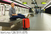 Купить «Modern girl sitting on bench at metro station», фото № 28511075, снято 27 апреля 2018 г. (c) Яков Филимонов / Фотобанк Лори