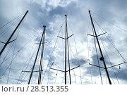 Купить «Ship masts over blue cloudy sky background», фото № 28513355, снято 29 апреля 2018 г. (c) Alexander Tihonovs / Фотобанк Лори