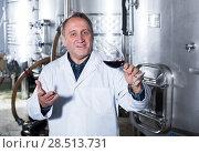 Купить «Wine maker controls quality of wine», фото № 28513731, снято 12 октября 2016 г. (c) Яков Филимонов / Фотобанк Лори
