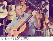 Купить «Man is playing on acoustic guitar», фото № 28513903, снято 18 сентября 2017 г. (c) Яков Филимонов / Фотобанк Лори