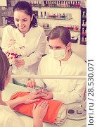 Купить «cheerful nail technician offering to female client to choose color of nail polish in beauty salon», фото № 28530071, снято 28 апреля 2017 г. (c) Яков Филимонов / Фотобанк Лори