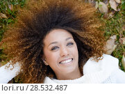 Купить «Beautiful young African American woman smiling with afro hairstyle and green eyes wearing white winter dress laying on the grass of an urban park», фото № 28532487, снято 25 ноября 2015 г. (c) Ingram Publishing / Фотобанк Лори