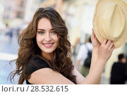 Купить «Happy young woman with blue eyes smiling in urban background. Girl wearing summer clothes and sun hat.», фото № 28532615, снято 26 апреля 2016 г. (c) Ingram Publishing / Фотобанк Лори
