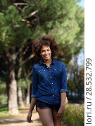 Купить «Young black woman with afro hairstyle walking in urban park. Mixed woman wearing blue shirt and shorts. Female smiling.», фото № 28532799, снято 10 декабря 2016 г. (c) Ingram Publishing / Фотобанк Лори
