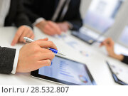 Купить «Close-up of a modern business team using tablet computer to work with financial data», фото № 28532807, снято 14 января 2014 г. (c) Ingram Publishing / Фотобанк Лори