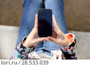 Купить «Young woman using a touchscreen smartphone wearing casual clothes», фото № 28533039, снято 17 ноября 2015 г. (c) Ingram Publishing / Фотобанк Лори