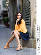 Купить «Young brunette woman with beautiful legs, model of fashion, wearing orange modern jacket and blue skirt, sitting in urban background», фото № 28533227, снято 11 марта 2017 г. (c) Ingram Publishing / Фотобанк Лори