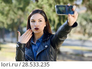 Купить «Portrait of a beautiful young woman selfie in the park with a smart phone. Girl blowing a kiss.», фото № 28533235, снято 12 декабря 2015 г. (c) Ingram Publishing / Фотобанк Лори
