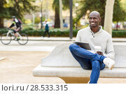 Купить «Black young man with tablet computer and take away coffee in urban background. Young african guy with shaved head wearing casual clothes.», фото № 28533315, снято 20 ноября 2016 г. (c) Ingram Publishing / Фотобанк Лори