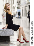 Купить «Blonde woman with beautiful legs in urban background. Beautiful young girl wearing black elegant dress and red high heels sitting on a bench in the street. Pretty russian female with long wavy hair hairstyle and blue eyes.», фото № 28533335, снято 24 января 2017 г. (c) Ingram Publishing / Фотобанк Лори