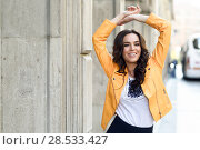 Купить «Young brunette woman, model of fashion, wearing orange modern jacket and blue skirt. Pretty caucasian girl with long wavy hairstyle smiling. Female raising her arms in urban background.», фото № 28533427, снято 11 марта 2017 г. (c) Ingram Publishing / Фотобанк Лори