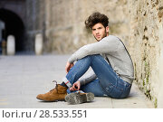 Купить «Portrait of young man wearing suspenders sitting on the floor in urban background», фото № 28533551, снято 8 апреля 2014 г. (c) Ingram Publishing / Фотобанк Лори