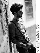 Купить «Portrait of young man wearing suspenders in urban background», фото № 28533735, снято 8 апреля 2014 г. (c) Ingram Publishing / Фотобанк Лори