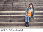 Купить «Young woman with nice hair wearing casual clothes in urban background. Happy girl with wavy hairstyle sitting in urban stairs.», фото № 28533751, снято 30 апреля 2017 г. (c) Ingram Publishing / Фотобанк Лори