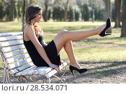 Portrait of funny woman, model of fashion with very long legs, sitting on a bench in an urban park, wearing black dress and high heels. Стоковое фото, фотограф Javier Sánchez Mingorance / Ingram Publishing / Фотобанк Лори
