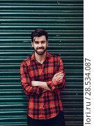 Купить «Young bearded smiling man wearing a plaid shirt with a green blind behind him. », фото № 28534087, снято 7 ноября 2017 г. (c) Ingram Publishing / Фотобанк Лори