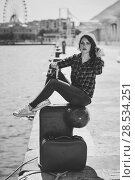Купить «Young woman taking photographs with a vintage camera sitting in a harbour. Girl wearing plaid shirt, blue jeans and sun hat. Black and white photograph.», фото № 28534251, снято 26 апреля 2016 г. (c) Ingram Publishing / Фотобанк Лори