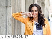 Купить «Young brunette woman, model of fashion, wearing orange modern jacket. Pretty caucasian girl with long wavy hairstyle. Thoughtful female in urban background.», фото № 28534427, снято 11 марта 2017 г. (c) Ingram Publishing / Фотобанк Лори