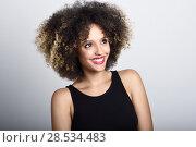 Купить «Young black woman with afro hairstyle laughing. Girl wearing black clothes. Studio shot.», фото № 28534483, снято 14 июня 2016 г. (c) Ingram Publishing / Фотобанк Лори
