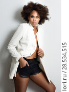 Купить «Young black woman with afro hairstyle possing near a white wall in her room. Mixed girl wearing blazer jacket and shorts.», фото № 28534515, снято 10 декабря 2016 г. (c) Ingram Publishing / Фотобанк Лори