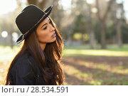 Купить «Portrait of thoughtful woman sitting alone outdoors wearing hat. Nice backlit with sunlight», фото № 28534591, снято 12 января 2016 г. (c) Ingram Publishing / Фотобанк Лори