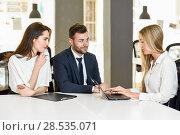 Купить «Blonde woman insurance agent or investment adviser explaining with laptop computer to a smiling young couple», фото № 28535071, снято 23 апреля 2017 г. (c) Ingram Publishing / Фотобанк Лори