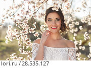Купить «Portrait of young woman smiling in the flowered garden in the spring time. Almond flowers blossoms. Girl dressed in white like a bride.», фото № 28535127, снято 10 марта 2015 г. (c) Ingram Publishing / Фотобанк Лори
