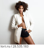 Купить «Young black woman with afro hairstyle possing near a white wall in her room. Mixed girl wearing blazer jacket and shorts.», фото № 28535183, снято 10 декабря 2016 г. (c) Ingram Publishing / Фотобанк Лори