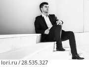 Young businessman near a modern office building wearing black suit and white shirt sitting on the floor. Man with blue eyes in urban background. Стоковое фото, фотограф Javier Sánchez Mingorance / Ingram Publishing / Фотобанк Лори