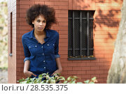 Купить «Young black woman with afro hairstyle standing in urban background. Mixed woman wearing blue shirt and shorts.», фото № 28535375, снято 10 декабря 2016 г. (c) Ingram Publishing / Фотобанк Лори