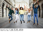 Multi-ethnic group of young people having fun together outdoors in urban background. group of people jumping together. Стоковое фото, фотограф Javier Sánchez Mingorance / Ingram Publishing / Фотобанк Лори