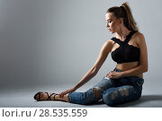 Купить «Young woman wearing black bra and blue jeans sitting on floor. Studio shot.», фото № 28535559, снято 25 июля 2017 г. (c) Ingram Publishing / Фотобанк Лори