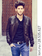 Portrait of a young handsome man, model of fashion, with modern hairstyle in urban background wearing blue jeans and leather jacket. Стоковое фото, фотограф Javier Sánchez Mingorance / Ingram Publishing / Фотобанк Лори