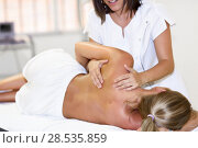 Professional female physiotherapist giving shoulder massage to blonde woman in hospital. Medical check at the shoulder in a physiotherapy center. Стоковое фото, фотограф Javier Sánchez Mingorance / Ingram Publishing / Фотобанк Лори