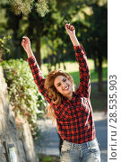 Beautiful woman raising arms with long blond curly hair. Enjoyment. Expressive Woman in checkered shirt and blue jeans smiling. Стоковое фото, фотограф Javier Sánchez Mingorance / Ingram Publishing / Фотобанк Лори