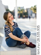 Dreamer blonde woman smiling in urban background. Beautiful young girl wearing striped t-shirt and blue jeans sitting on a bench in the street. Pretty russian female with pigtail and eyes closed. Стоковое фото, фотограф Javier Sánchez Mingorance / Ingram Publishing / Фотобанк Лори