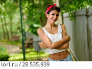 Купить «Portrait of a pin-up girl. American style, in a garden, wearing jeans and t-shirt», фото № 28535939, снято 20 мая 2012 г. (c) Ingram Publishing / Фотобанк Лори