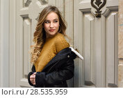 Купить «Blonde woman in urban background. Beautiful young girl wearing black leather jacket and mini skirt standing in the street. Pretty russian female with long wavy hair hairstyle and blue eyes.», фото № 28535959, снято 24 января 2017 г. (c) Ingram Publishing / Фотобанк Лори