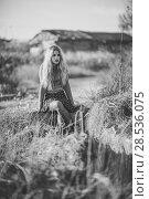 Купить «Beautiful young blonde woman, model of fashion, in rural background. Girl wearing sweater and skirt. Black and whit shoot.», фото № 28536075, снято 17 ноября 2015 г. (c) Ingram Publishing / Фотобанк Лори