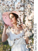 Купить «Portrait of young woman in the flowered field in the spring time. Almond flowers blossoms. Girl wearing white dress and pink sun hat», фото № 28536115, снято 10 марта 2015 г. (c) Ingram Publishing / Фотобанк Лори