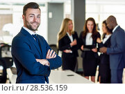 Купить «Caucasian businessman leader looking at camera in modern office with multi-ethnic businesspeople working at the background. Teamwork concept. Young man with beard wearing blue suit.», фото № 28536159, снято 23 апреля 2017 г. (c) Ingram Publishing / Фотобанк Лори