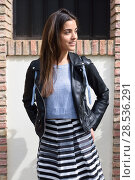 Купить «Portrait of young woman smiling in urban background wearing casual clothes. Girl wearing striped skirt, sweater and leather jacket», фото № 28536291, снято 14 апреля 2015 г. (c) Ingram Publishing / Фотобанк Лори