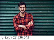 Купить «Young smiling man, model of fashion, wearing a plaid shirt with a green blind behind him. », фото № 28536343, снято 7 ноября 2017 г. (c) Ingram Publishing / Фотобанк Лори