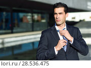 Купить «Young handsome businessman, dressed in blue suit, adjusting a tie in urban background with modern office buildings. Caucasian man with blue eyes.», фото № 28536475, снято 17 ноября 2016 г. (c) Ingram Publishing / Фотобанк Лори